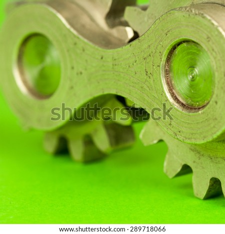 Double joint machinery part of two cylindrical metal cogwheel fragments spinning together thus moving ahead, symbolizing thinking concept and mechanical approach to kinetic movement problems and terms - stock photo