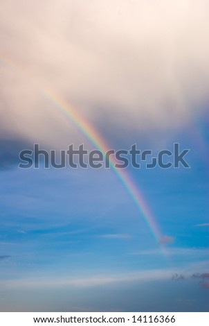 Double Rainbow Extending Below Base of Clouds in Blue Sky - stock photo