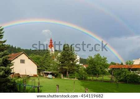 Double rainbow over a church in a cloudy village. Traditional farm with church in a village and double rainbow over woods and trees - stock photo