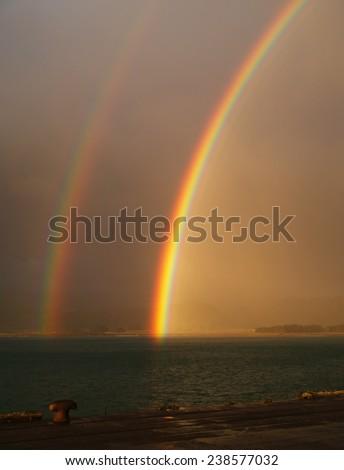 Double rainbow over Hicks Bay, New Zealand - stock photo