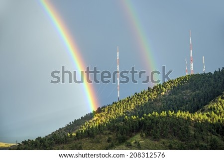 Double Rainbow Over the Mountain with Broadcast Antennas. Colorful Summer Rainbow.