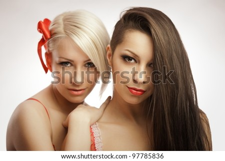 Double sensual portrait of blond and brunette - stock photo