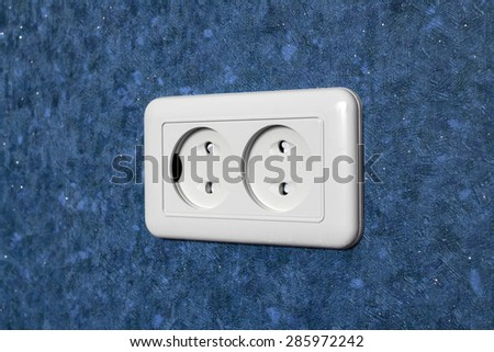 Double socket located horizontally on the wall with blue wallpaper