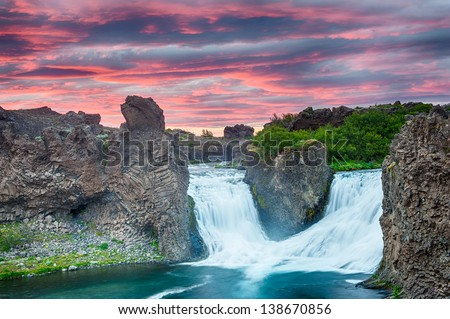 Double waterfall Hjalparfoss on the river Fossa after the midnight sunset with a beautiful vivid dramatic sky and basalt rocks - stock photo