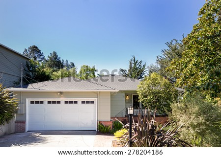Double white painted garage doors exterior in new painted house. - stock photo
