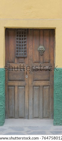 Double Wooden Doors-colorful green and yellow wall, with double doors made of carved wood and other decorative elements, and a knocker shaped like a sun, with a happy face, in San Miguel de Allende