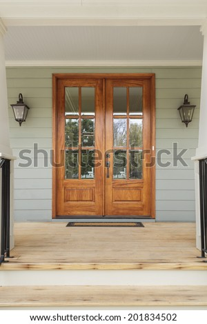 Double wooden doors to a green home. The doors have windows, and are flanked by twin light fixtures. Also seen is a doormat, and a wooden porch. - stock photo