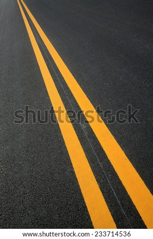 Double yellow lines on the asphalt road, closeup of photo