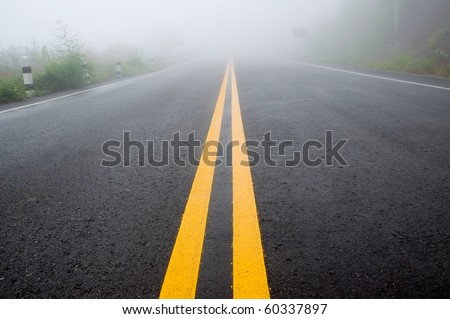 double yellow lines on the road with fog - stock photo