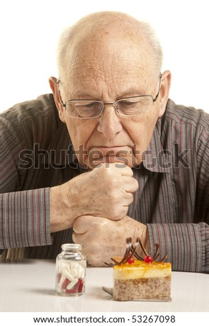 Doubtful senior man looking at a cake and a bottle of pills