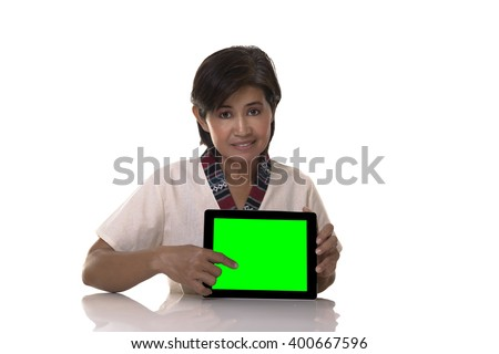 Doubtful woman wearing white blouse with patterned trim and holding tablet points to screen - stock photo