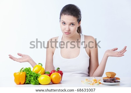 Doubting the girl with a healthy diet and sweet on a white background - stock photo