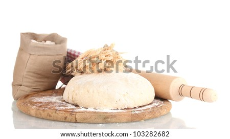 Dough and bags with flour on wooden board isolated on white - stock photo