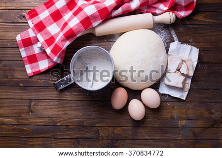 Dough and ingredients for it - eggs, flour, yeast on dark painted  wooden background. Selective focus. Place for text.  - stock photo