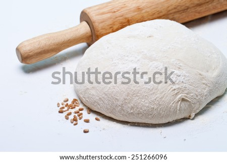 Dough and rolling pin over white background - stock photo