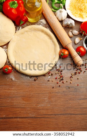 Dough basis and ingredients for pizza, on the table - stock photo