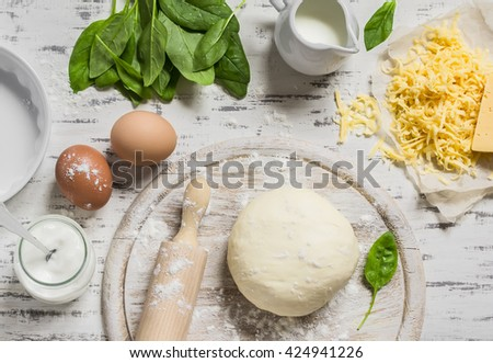 Dough, eggs, fresh spinach, cheese - raw ingredients to prepare pie with spinach, cheese and egg. On a light wooden background. Baking background - stock photo