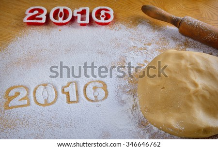 Dough, flour and rolling pin on wooden table with New Year numbers 2016.