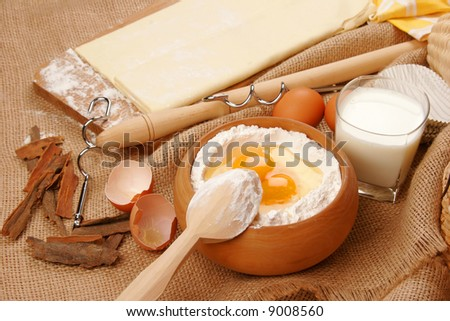 Dough for baking and a bowl of flour with eggs. - stock photo