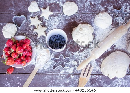 Dough for cookies, ripe strawberry and berries of a honeysuckle. Food composition on a wooden background. Top view - stock photo