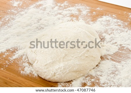 Dough in flour on wooden board. - stock photo