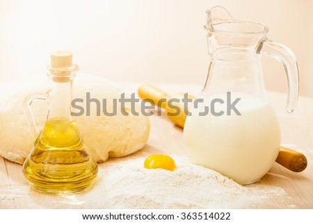 dough on a board with flour. olive oil, eggs, rolling pin