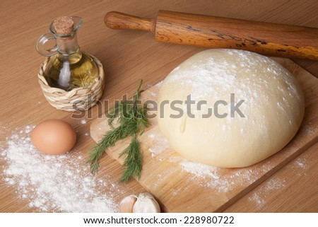 dough on a board with flour. olive oil, eggs, rolling pin, garlic and dill - stock photo