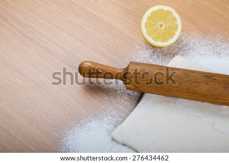 Dough, rolling pin, half of lemon and flour sprinkled on a light wooden table.
