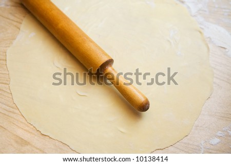 Dough with circle rolling pin - stock photo