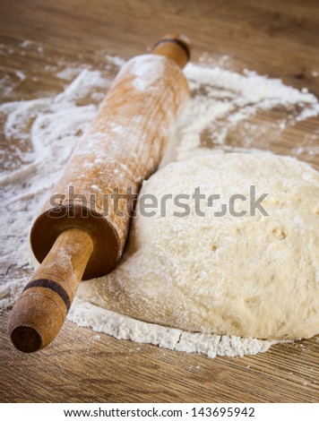 Dough with rolling pin on wooden table - stock photo