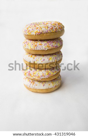 Doughnut are stacked in a column. Donuts for tea. Tasty food cakes. Delicious classic cakes: fried doughnuts glazed with caramel. Nutritious dish that promotes obesity. - stock photo