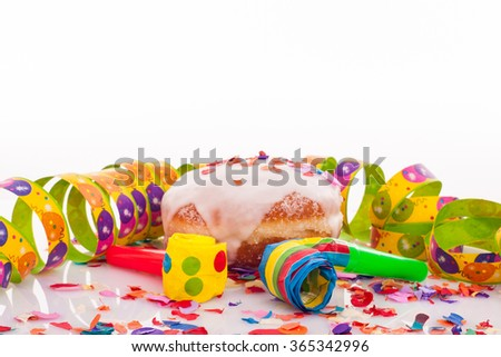 doughnut with frosting, confetti, streamer and noisemaker - carnival decoration with copy space on upper section of picture