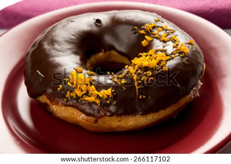 doughnut with orange  on marsala color plate - stock photo