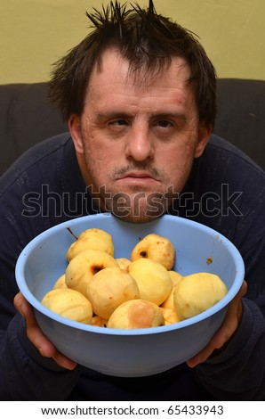 down syndrome man with apples - stock photo