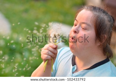 down syndrome woman blowing dandelion - stock photo