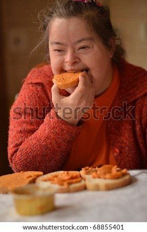 down syndrome woman eating - stock photo