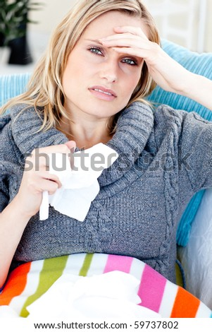Downcast woman lying on a sofa with tissues and feeling her temperature against a white background - stock photo