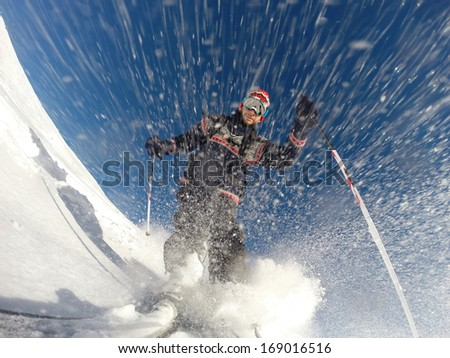 Downhill alpine skiing at high speed on powder snow. Taken with GoPro 3 mounted directly on the ski tip. Model released. - stock photo