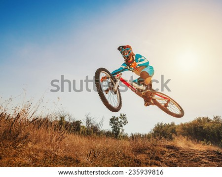 Downhill cycling. Man high jump on a mountain bike. Extreme sport. - stock photo
