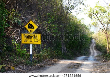 Downhill dust road with thai road sign