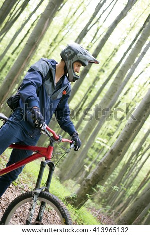 Downhill mountain bike. Young man cyclist to riding a bicycle. Mountainbiker rides in spring forest - stock photo