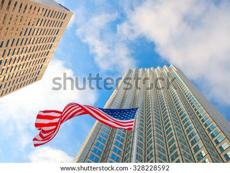 Downtown buildings and waving American flag, low perspective view