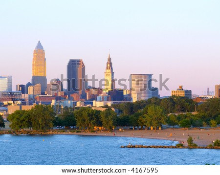 Downtown Cleveland, Ohio, lit by the setting sun, with beach in foreground - stock photo