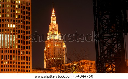 Downtown Cleveland Ohio's Terminal Tower lit up at night, framed by the Justice Center and a raised lift bridge