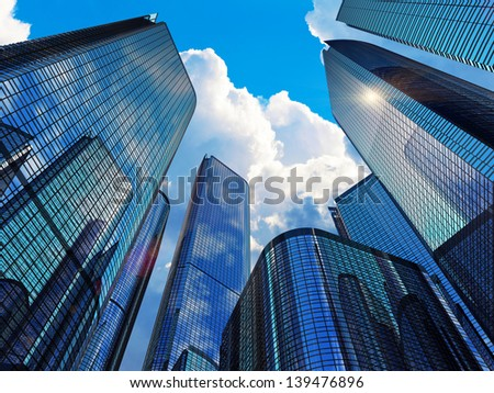 Downtown corporate business district architecture concept: glass reflective office buildings skyscrapers against blue sky with clouds and sun light - stock photo