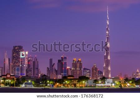 Downtown Dubai (UAE, United Arab Emirates) in violet spectacular nice sunset. Burj Khalifa, the tallest building in world.  Amazing beautiful modern skyscrapers  built in desert. Skyline from beach.  - stock photo