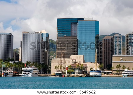 Downtown Honolulu Skyline with boats and skyscrapers fronting Honolulu Harbor - stock photo