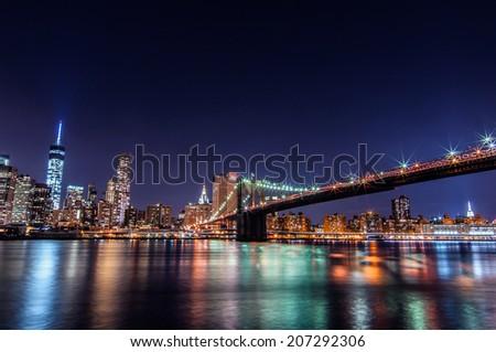 Downtown Manhattan night view from Brooklyn Bridge Park - stock photo