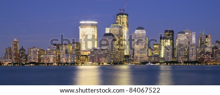 Downtown Manhattan viewed from across the Hudson RIver at night. - stock photo