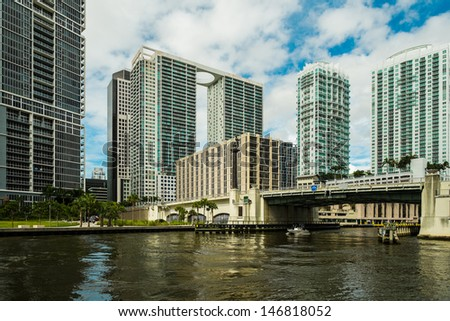 Downtown Miami along the Miami River inlet with Brickell Avenue bridge and condominiums in the background. - stock photo